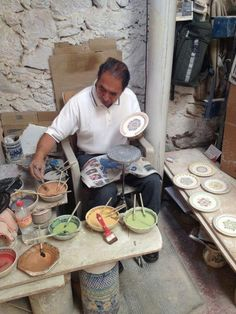 Artist hand painting ceramic dishes in Gorky's Mexico workshop. Love all the glazes and how each plate is slightly different. #ceramics #pottery