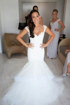 Fitted lace and tulle wedding dress with cap sleeves, sweetheart neckline, and layered skirt