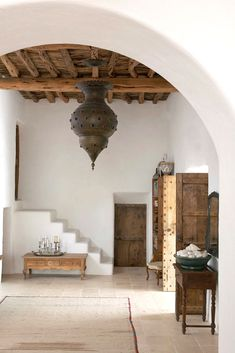 White walls, rounded arches, studded wooden doors, exposed beams