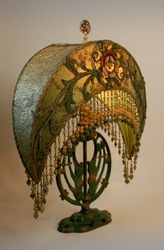 Wonderful circa 1915 cast lamp base with original paint. The large Craftsman crescent shade is created with original Arts & Craft textiles in gold and green tones including antique bronze-gold metallic lace, net lace and an ornate period William Morris style rose and vine appliqué. Hand beaded custom fringe in accent colors of olive, earth tones and rose adorns the bottom of the shade.    This lamp would look great in a mission, bungalow or cottage style home.