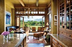 Locati Architects designed a home that responds to landscape and lifestyle - A Rocky Hawkins painting sets the mood for the kitchen nook, which opens via an accordian glass door to the outdoor living areas. Photo By: Rodger Wade    www.westernartandarchitecture.com