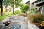 "The stone seating and patio area work so well to define the boundaries between the ""civilized"" area and the wilder backdrop of lawn and trees. Just stunning and so well-suited to the property. Design by Gregg and Ellis Landscape Design."