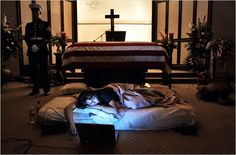 """The night before the burial of her husband's body, Katherine Cathey refused to leave the casket, asking to sleep next to his body for the last time. The Marines made a bed for her, tucking in the sheets below the flag. Before she fell asleep, she opened her laptop computer and played songs that reminded her of """"Cat."""" Photo: Todd Heisler/Rocky Mountain News"""