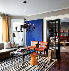 Living room - love that gray/greige paint and the leather chairs. Spot of royal blue is interesting.