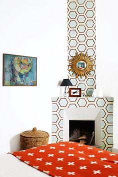 Tour a Pattern-Packed Coastal Bungalow in Morocco // bedroom, orange blanket, hexagonal Popham Design tiles, starburst mirror, fireplace, wicker basket