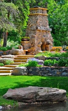 Evergreen Residence  Hand-crafted stonework to create a dramatic outdoor fireplace