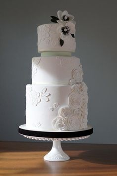 Elegant rosettes cascade down this all-white wedding cake, while piped flowers scatter the opposite side.