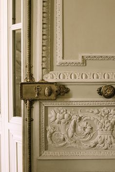 Beautiful carved door with decorative brass hardware.