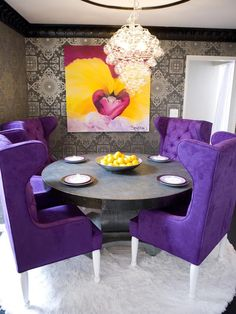 This colorful dining room is sophisticated and dramatic. A white faux fur rug sits on top of black leather flooring, and the spiral chandelier brings whimsy to the space. The graphic wallpaper and artwork by David Bromstad add extra punches of texture and color.