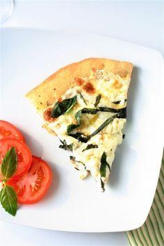 Four cheese white pizza with fresh basil, thyme, and oregano.