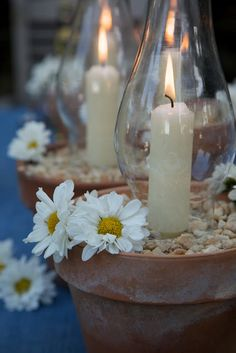 casual centerpieces made with pots, glass chimneys, candles, daisies, and pebbles...love the simplicity...