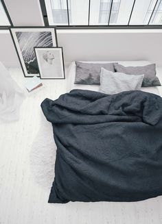 With it's monochrome scheme and simply made bed in layers from white to black that hug large, uncovered windows. Looks like the sort of place you'd want to take a long Sunday nap and forget the world around you. The kind of bedroom you wouldn't mind spending the entire day in.
