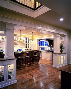 Dining room opening with built-ins below the columns.