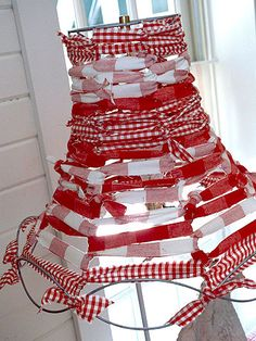 For a DIY shade, scout out an old wire lampshade frame. Cut narrow strips of different patterned fabric in coordinating colors. Starting at the top, wrap a strip of fabric around one of the metal spines, then stretch it over to the next one, working your way around the frame. Simply knot one strip to another as needed. Continue down to the base of the frame, securing strips with hot glue.