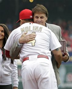 St. Louis Cardinals' Yadier Molina (4) gets a hug from former manager Tony La Russa after receiving his 2011 World Series championship ring from Jostens.