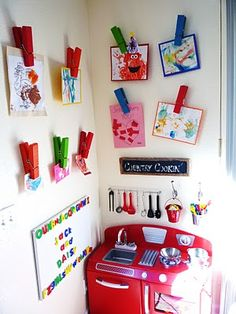 Giant clothes pins velcro'd to the wall for kids artwork display