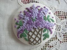 Lilac French-knot covered button.