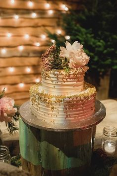 ivory wedding cake with gold beads, photo by Lauren Fair Photography http://ruffledblog.com/terrain-winter-wedding #cakes #weddingcake #wedding