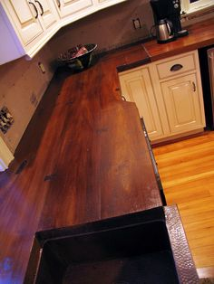 Concrete Countertop - Cast on a wood plank mold and stained to look like wood. Interesting.