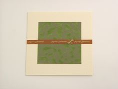 Christmas Dragonfly - This soft and gentle cream hammer folded card has a distinctive felt texture inside and out. Conveying both warmth and high quality. Design features the decorative designer paper and a printed 'merry christmas' brown satin ribbon detail runs through the front of the card. Finishing touch: metal dragon fly. It comes with white envelope in protective cellobag.