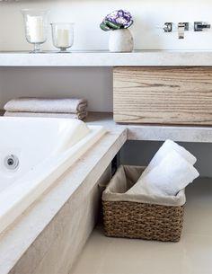 Dúplex em Porto Alegre com ambientes integrados. -- A textura fosca do limestone, que reveste a bancada e a caixa da banheira de hidromassagem (Axell), e o piso de porcelanato brilhante (Portinari) seguem a paleta de cores neutras do quarto do casal. No vão entre as bancadas, o gavetão de madeira oculta compartimentos para maquiagem e itens de higiene.