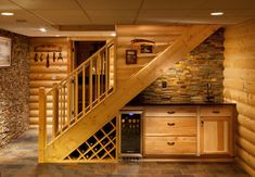 Cleverly tucked beneath the stairs, this wet bar ensures that one rarely has to leave the basement. The custom built-ins include a wine rack...
