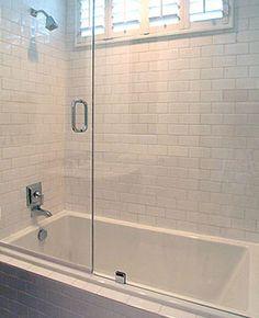 Clean, crisp white bathroom with white beveled subway tiles shower surround, glass sliding shower doors and polished nickel shower kit..