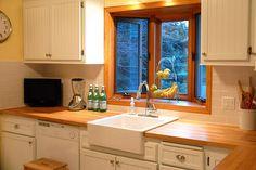 white cabinets, butcher block counter, white subway backsplash
