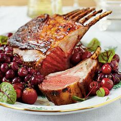 Honey-Curry Glazed Lamb with Roasted Grapes and Cranberries | A honey-curry glaze elevates this lamb to a whole new level. Roasted grapes and cranberries add a festive and tasty touch to this impressive meal. | SouthernLiving.com