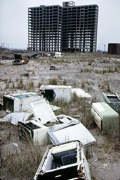 NY, 1973.  Skeleton of apartment building never completed, abandoned refrigerators and a burned out 1965 Ford Mustang. Breezy Point, Queens looking toward Brooklyn. New York.