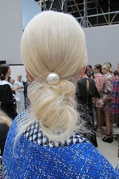 A chic swirled bun cinched with an oversized pearl, as seen at Chanel Spring 2013