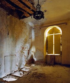 Light shines through a boarded-up window onto the rotting plastered walls