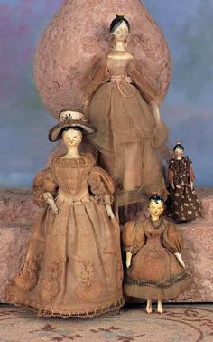 """Four Early Grodnertal Wooden Dolls in Original Costumes. 8"""" largest. Each is carved wooden doll with painted black hair with stippled details around the face, yellow """"tuck comb"""" at crown, painted facial features, articulated dowel-jointed shoulders, elbows, hips & knees, painted flat shoes. Condition: very good,each with well-preserved original finish albeit some typical rubs and few chips in hair and combs. Circa 1840."""