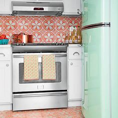 Tropical Kitchen | A mint green refrigerator and Moroccan tiles on the floor and backsplash add punch to this kitchen. | SouthernLiving.com