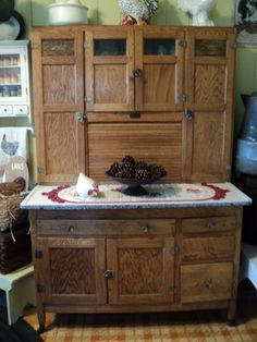 Hoosier cabinet~More ornate than most. We had one in our home until Dad built cabinets...it was great, had a 50# flour bin w/a built-in sifter behind the left door.  Mom made some great bread and cakes at that enameled counter.  Ours was painted white.  Nice memories
