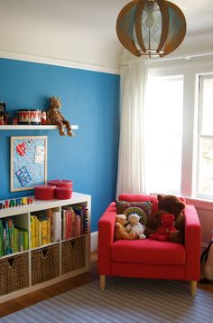 Sweet little toddler bedroom - I like how the books are organized by color.  We could also move the girls' PBK armchairs into their separate rooms for a reading nook.