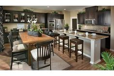 Glass-fronted black cabinets contrast with gray and tan in this spacious kitchen and eating area. The La Bella model by Beazer Homes. The Enclave at Crafton Hills community. Yucaipa, CA.