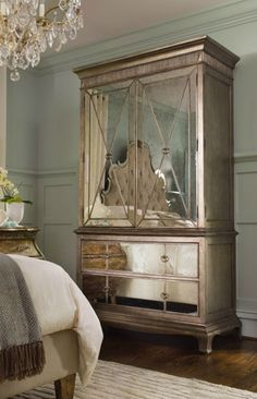 Traditional bedroom with a mirrored armoire and crystal chandelier