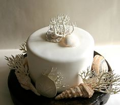 Adorn a cake for a beach wedding with handmade sugar coral and chocolate seashells.