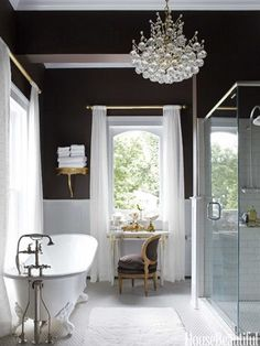 black bathroom walls with the all white tub, sink, toilet, tile