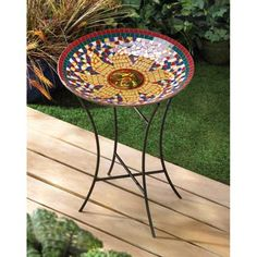 """Radiant Sun Birdbath $41.91 + Free Shipping The colorful mosaic bowl and the sleek, modern metal stand make this birdbath a contemporary classic.  The wise face of this sun surrounded by jewel-toned tiles will brighten the water, attracting birds to take a break from flitting and flying to cool off in your yard. Overall:  15"""" x 15"""" x 21"""" high.  Birdbath:  15"""" diameter x 2 1/2"""" high.  Stand:  20"""" high.  Iron and glass."""