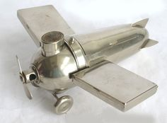 """This very rare German art deco smoker's companion in the form of an airplane was designed ca. 1930 for J.A. Henckels, Solingen, Germany. The airplane includes a hinged compartment in the center for cigars, two removable cigarette cases as wings, a set of four ashtrays behind the match safe with striker that is the cockpit. The propeller is spring loaded as a cigar clipper which drops the cutting into the wheel carriage. Stamped """"Germany"""". The airplane 9 ¾"""" long, 5"""" high and the wing span 10.5"""""""