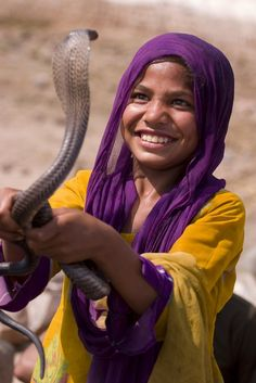 Cobra Girl- A girl belonging to a tribe of nomads in Pakistan fearlessly stares at a cobra. The tribe wrangles poisonous snakes and sells their venom.  Location: Burj Attari, Pakistan