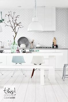 Kitchen and dining area in white with blue accents photographed by Paulina Arcklin