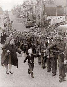 """""""Espere por mim, papai"""" é uma das fotografias mais famosas da Segunda Guerra Mundial. Foi tirada em 1940 em Westminster, Canadá, quando Claude Dettloff marchava para a guerra. Warren Bernard. de 5 anos de idade, fugiu de sua mãe para dar um último adeus a seu pai. Esta fotografia foi destaque na revista Life."""