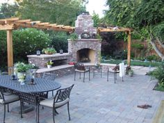 This brick outdoor fireplace adds year round entertainment and living space to the garden.  Complementary color tints from the concrete pave...