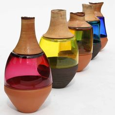 Each of these vases combines turned wood, blown glass and thrown pottery.