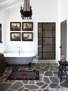 love the way this looks retrofitted into a historic building...stone floor, steel shower door, plank/exposed rafter ceiling & vintage tub.  love the bird prints.  elegant and masculine but organic. Designer Bathrooms and Pictures - Bathroom Decorating Ideas - House Beautiful