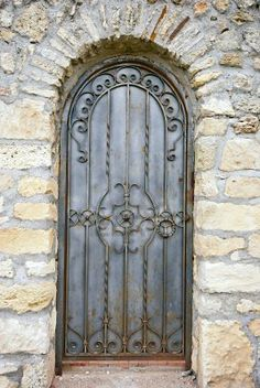 stone wall..arched doorway.....door with iron scrollwork...