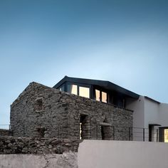 """Residential Architecture: Cabrela House by Orgânica Arquitectura: """"..Lisbon studio Orgânica Arquitectura have completed a two-storey residence behind the solid stone walls of an otherwise ruined house in Sintra, Portugal..A wall of windows at the rear of CabrelaHouse overlooks a small courtyard, which is bounded by the retained stone structure..The new steel-framed house has a pitched roof that imitates the profile of both the existing building and the adjoining property next door..A living roo"""